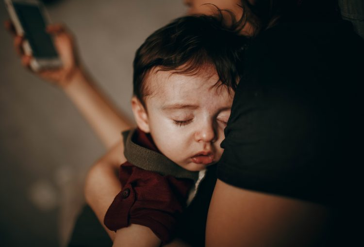 shows sick child in mothers arms